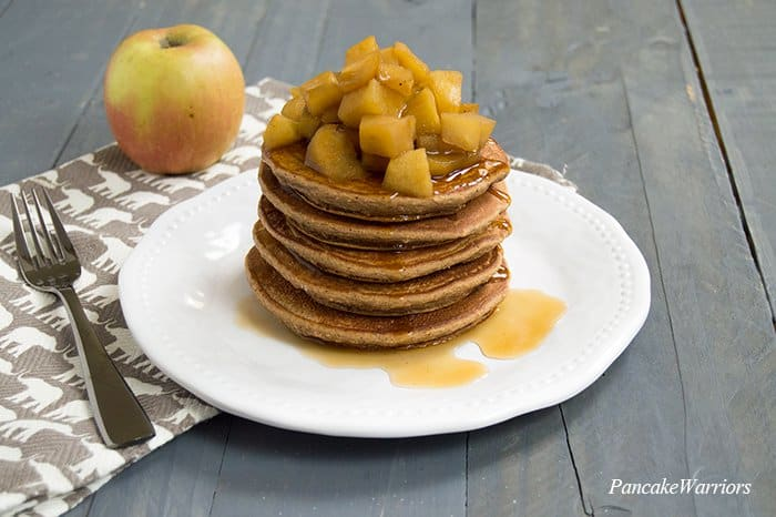 Spiced Apple Oat Protein Pancakes stacked high with syrup