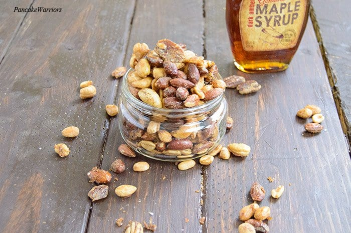 maple candied mix nuts overflowing from a mason jar