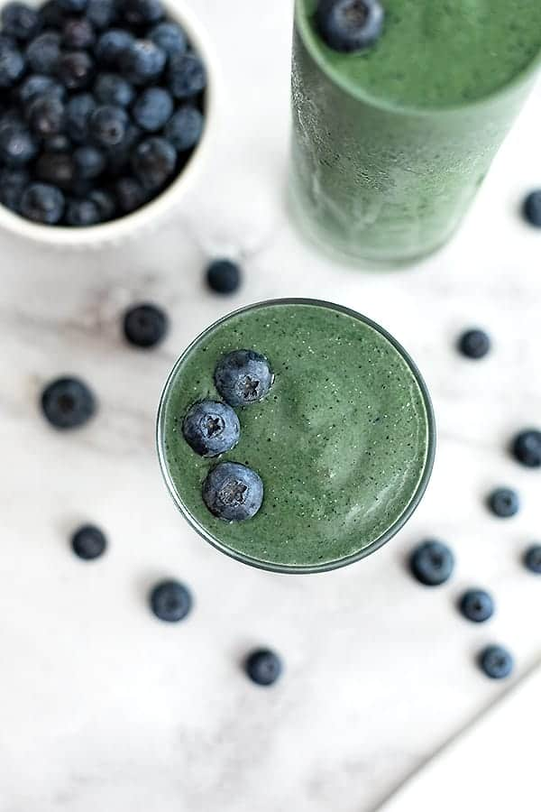 Looking down on a glass full of spinach blueberry smoothie