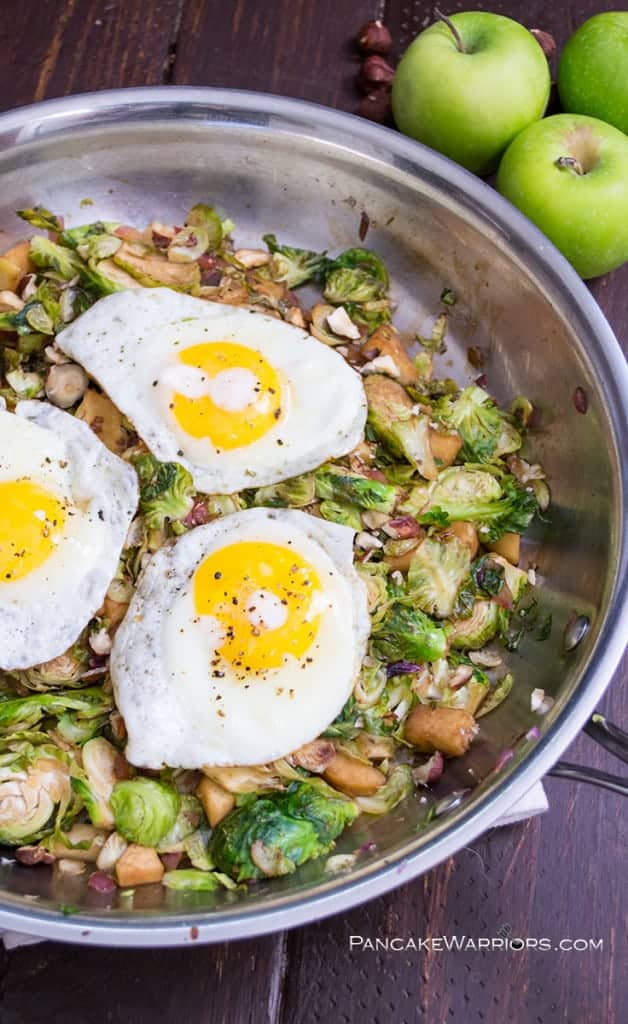 Apple Brussels Sprouts Hash in a skillet with 3 eggs on top.