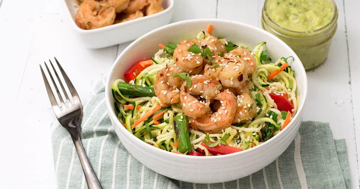 ginger garlic shrimp zoodle bowl with avocado cilantro dressing