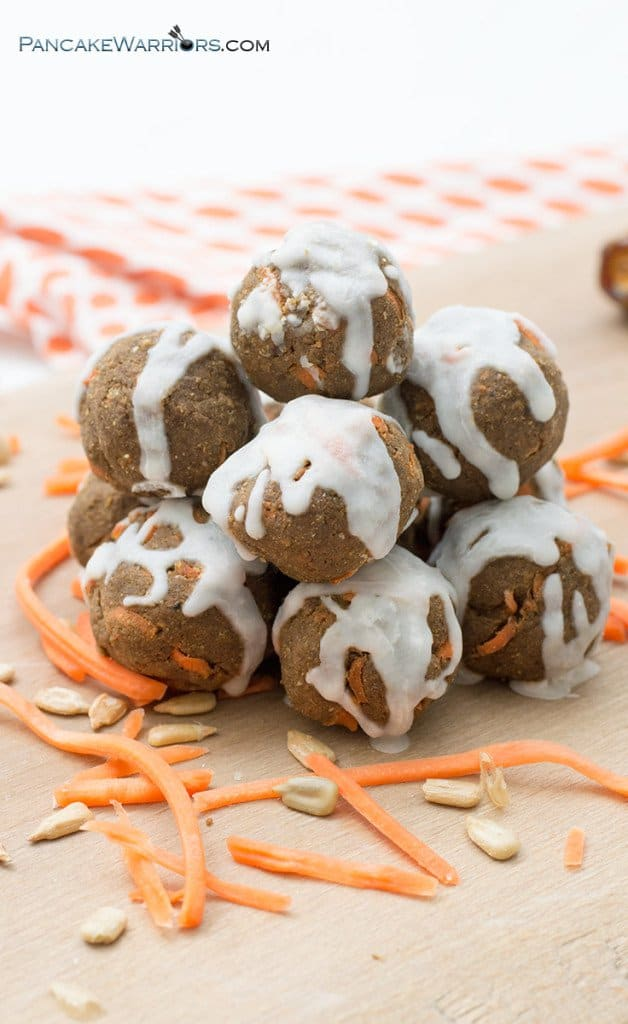 no-bake carrot cake energy bites in a pile with carrot strips