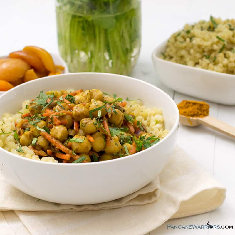 apricot chickpea curry piled high in a bowl with cauliflower rice, curry and apricots