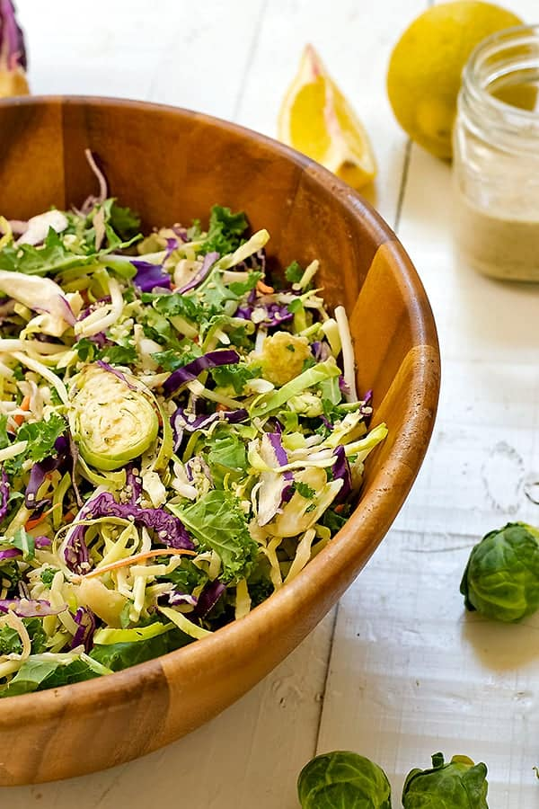 cruciferous crunch salad in a wooden salad bowl, brussels around the bowl