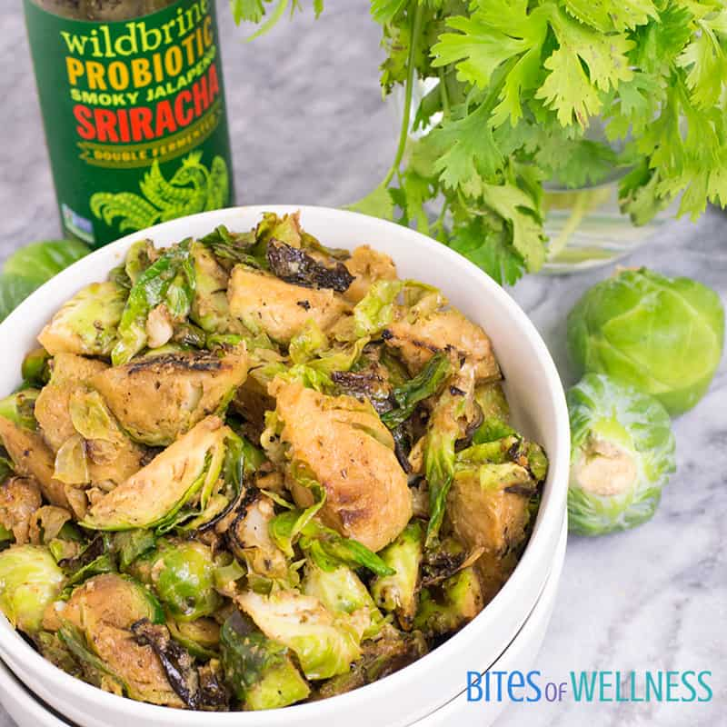 a bowl of whole30 spicy sriracha brussels sprouts with sriracha bottle