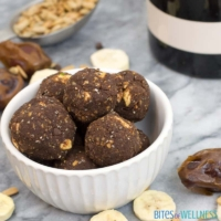 Double chocolate banana protein energy bites piled high in a bowl with banana, dates and sunflower seeds