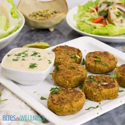 Curried salmon cakes on a serving plate with a bowl of cilantro lime yogurt sauce