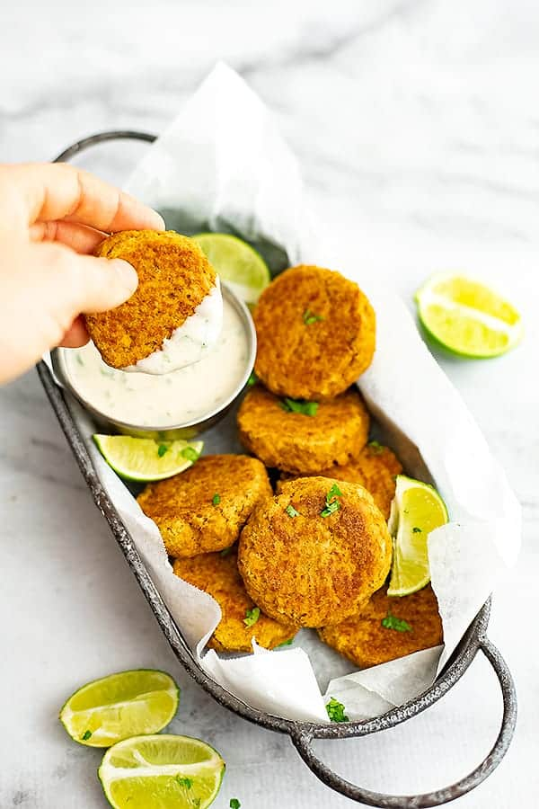 Curry salmon cake being dipped in cilantro lime yogurt dip