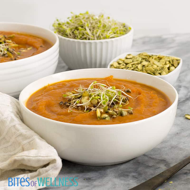 Two bowls of slow cooker curried butternut squash soup with sprouts and pumpkin seeds