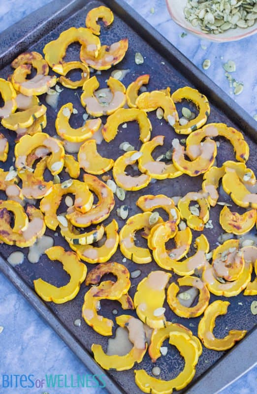 This roasted delicata squash with maple tahini drizzle is the perfect fall side dish, ready in under 30 minutes! Paleo, gluten free, grain free and vegan | bitesofwellness.com