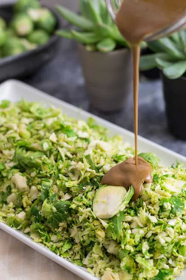 Balsamic dressing being poured on shaved brussels sprouts salad