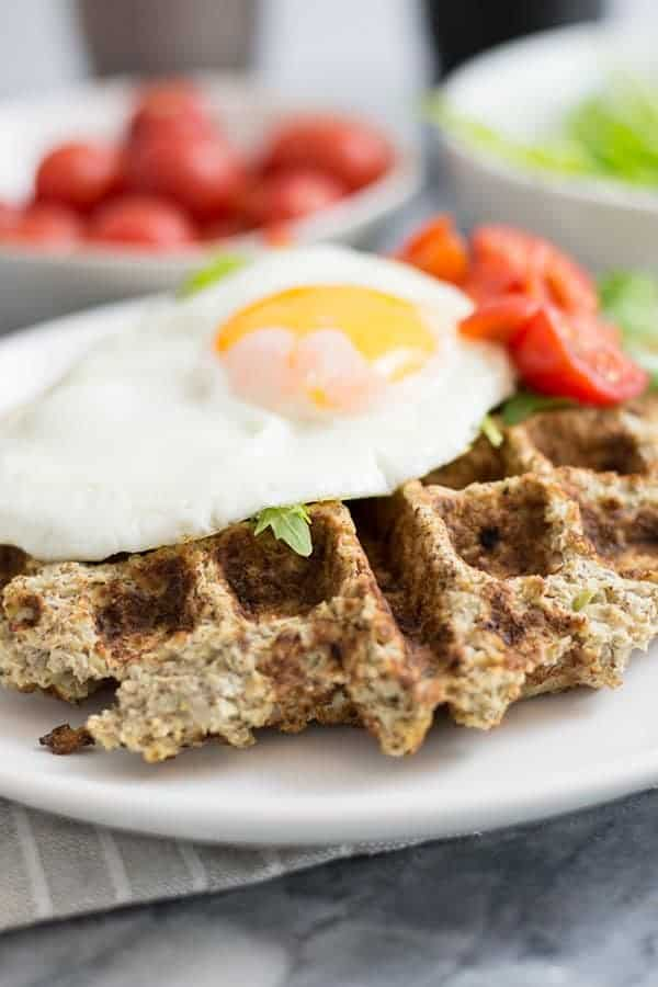 These simple low carb savory cauliflower waffles are going to become your favorite breakfast recipe! Paleo, whole30, vegetarian and low carb! So simple and filling! #paleo #whole30 #waffles #breakfast