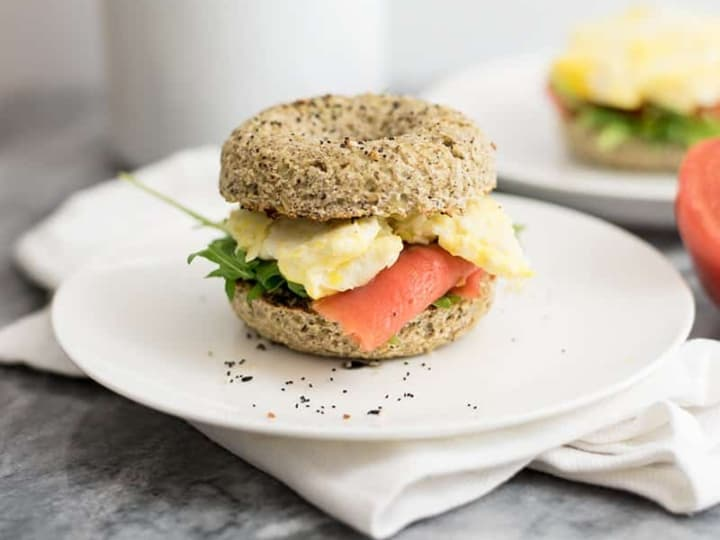 Cauliflower low carb bagels stuffed with egg, smoked salmon and arugula on a white plate over a white napkin