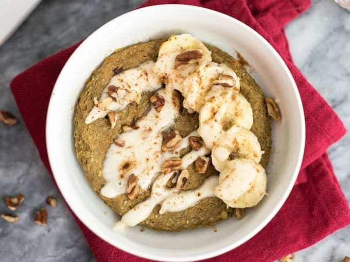 White bowl of gingerbread mug cake over a red napkin topped with sliced bananas, chopped pecans and coconut butter drizzle