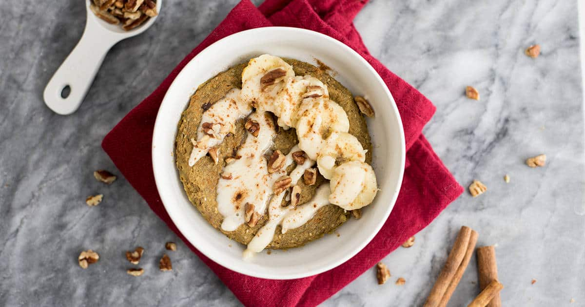 Gingerbread mug cake with cut up banana, nuts and coconut butter drizzle