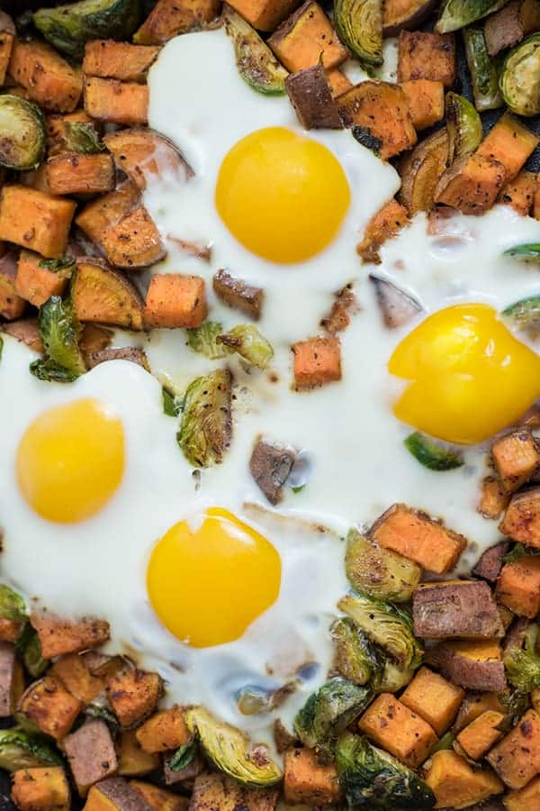 Close up picture sweet potato breakfast hash with brussels sprouts and eggs in an iron skillet