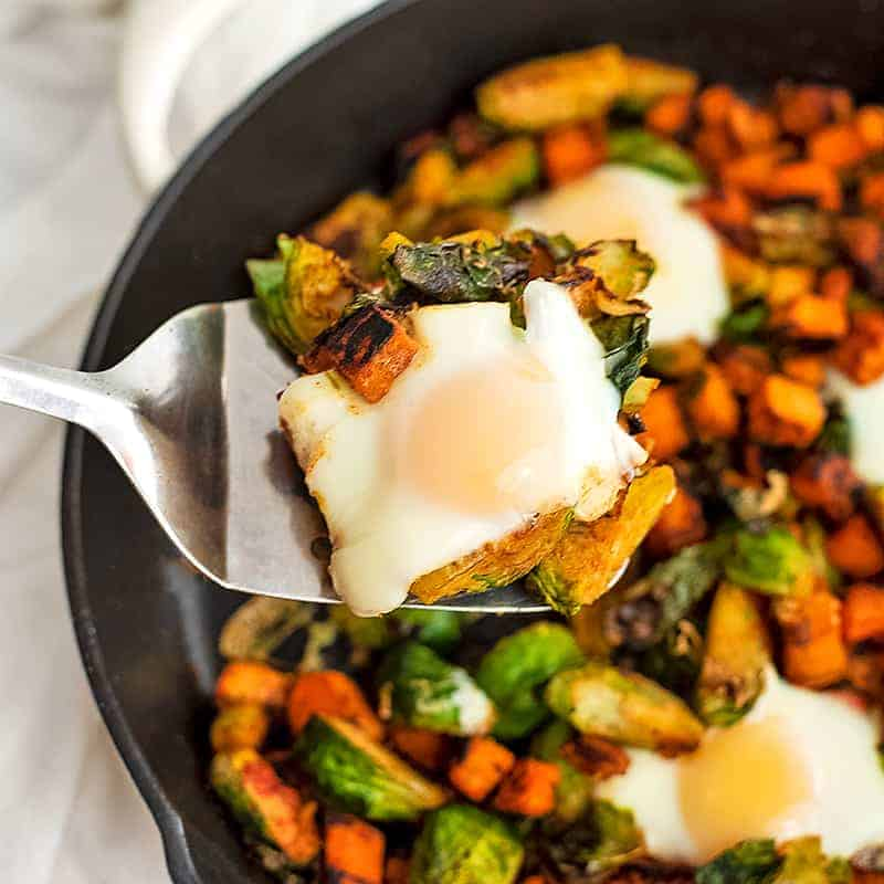 Sweet potato breakfast hash with brussels sprouts and eggs in an iron skillet