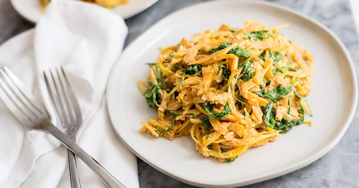 butternut squash noodles with a creamy garlic sauce with arugula on white plate with fork