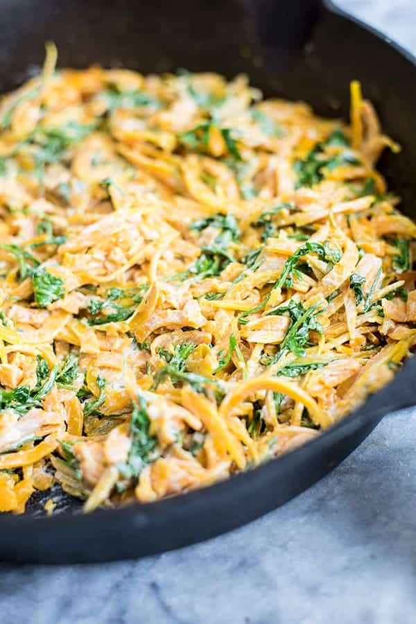 butternut squash noodles with a creamy garlic sauce with arugula in a cast iron skillet