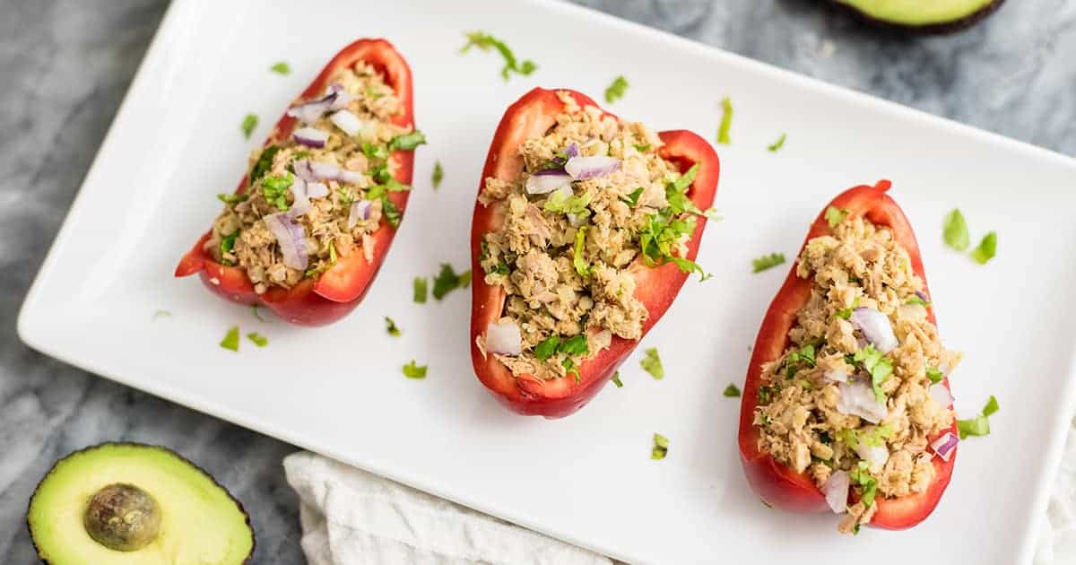 Tuna Stuffed Peppers on a white serving tray with avocado