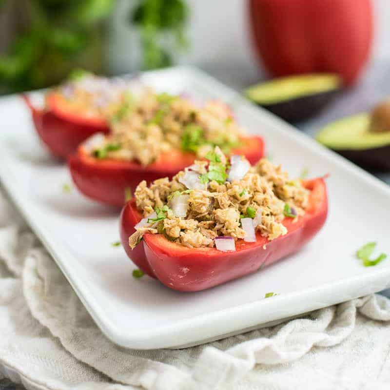 Tuna Stuffed Peppers on a white serving tray with avocado, red bell pepper and cilantro