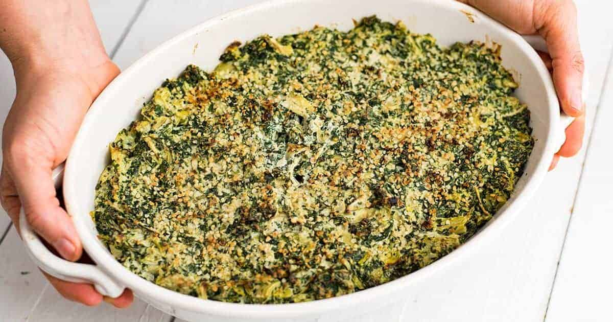 Hands holding Spinach Artichoke Dip in a white casserole dish