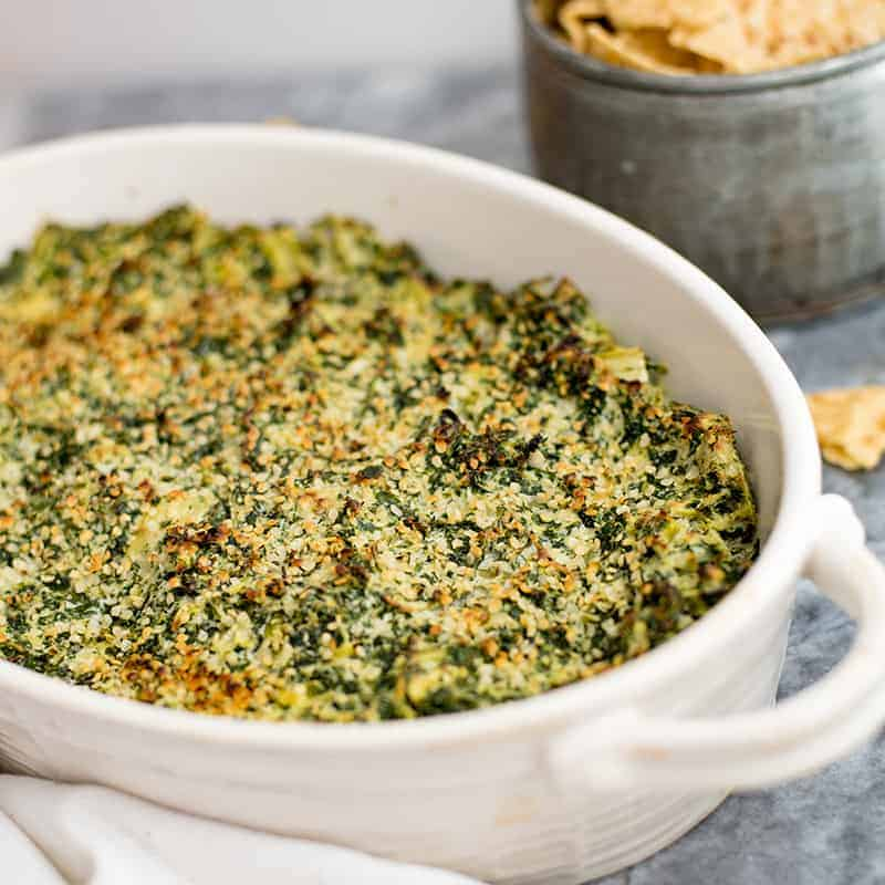 Spinach Artichoke Dip in a white casserole dish with chips