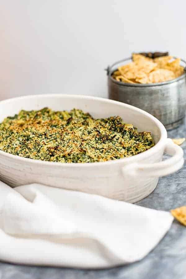 Spinach Artichoke Dip in a white casserole dish with chips and white napkin