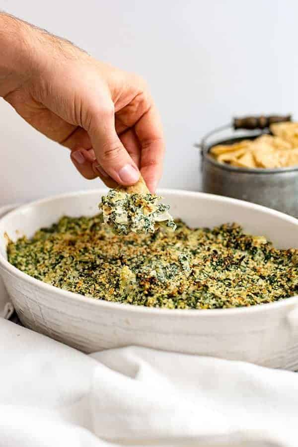 Hand dipping chip into spinach artichoke dip in a white casserole dish