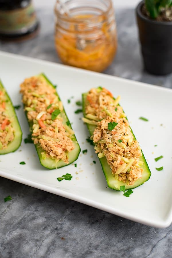 buffalo salmon in cucumber boats on white plate with buffalo sauce