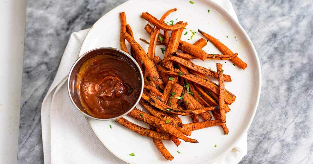 Carrot fries over a white plate with a side of ketchup in a silver bowl over a white napkin