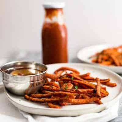 Carrot fries over a white plate with a side of ketchup in a silver bowl over a white napkin. Ketchup in the background