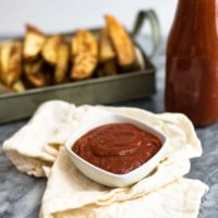 White ramekin filled with homemade ketchup in the center, a bottle of homemade ketchup and french fries in the background