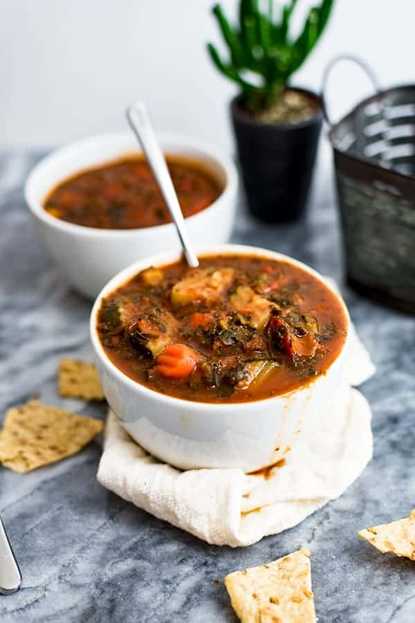 Mediterranean Vegetable Soup in a white bowl with spoon in bowl of soup.