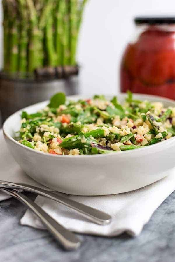 White bowl filled with asparagus spring salad with asparagus and roasted red pepper in the back