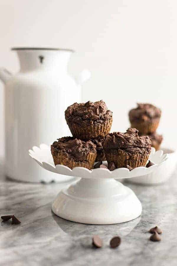 Vegan Chocolate Protein Muffins stacked on a white cake stand with a white jar in the background