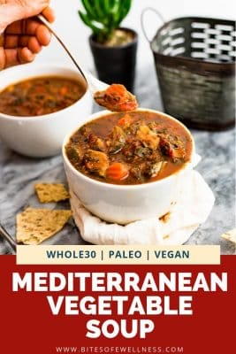 Mediterranean Vegetable Soup in a white bowl with spoon of soup overhead