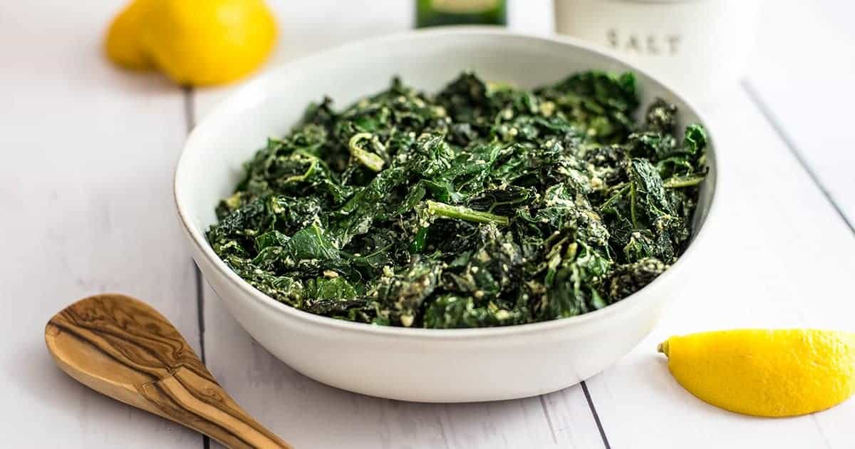 Large bowl of creamy kale with a lemon wedge to the side and a wooden spoon