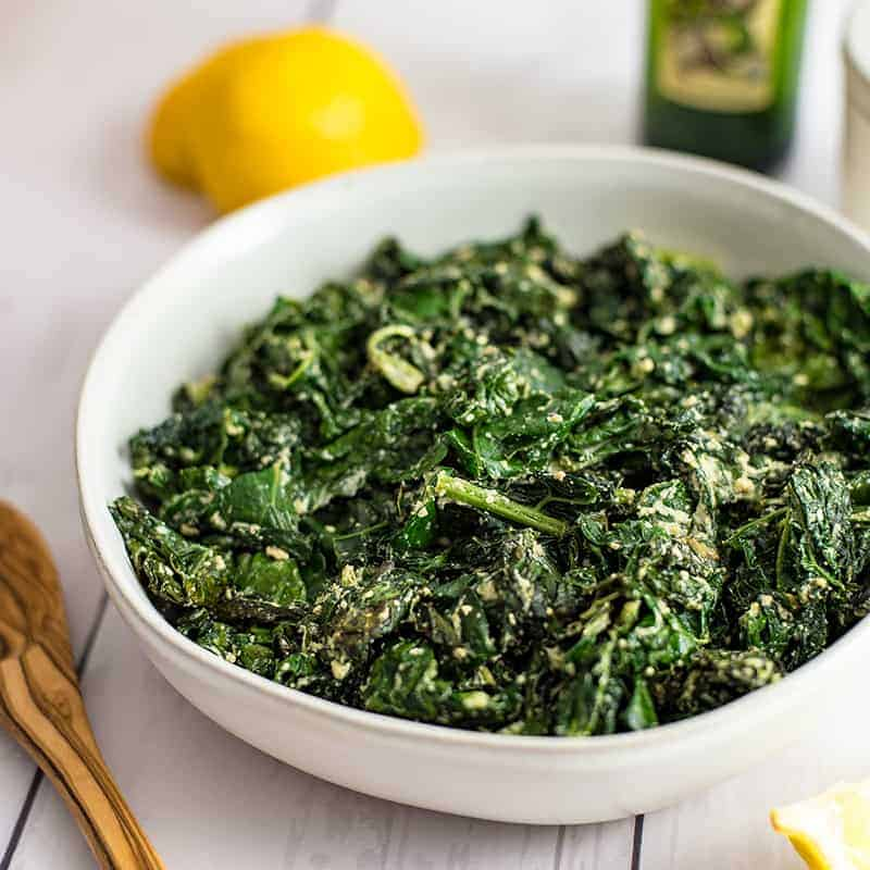 Large bowl of creamy kale with a juiced lemon and a bottle of olive oil in the background