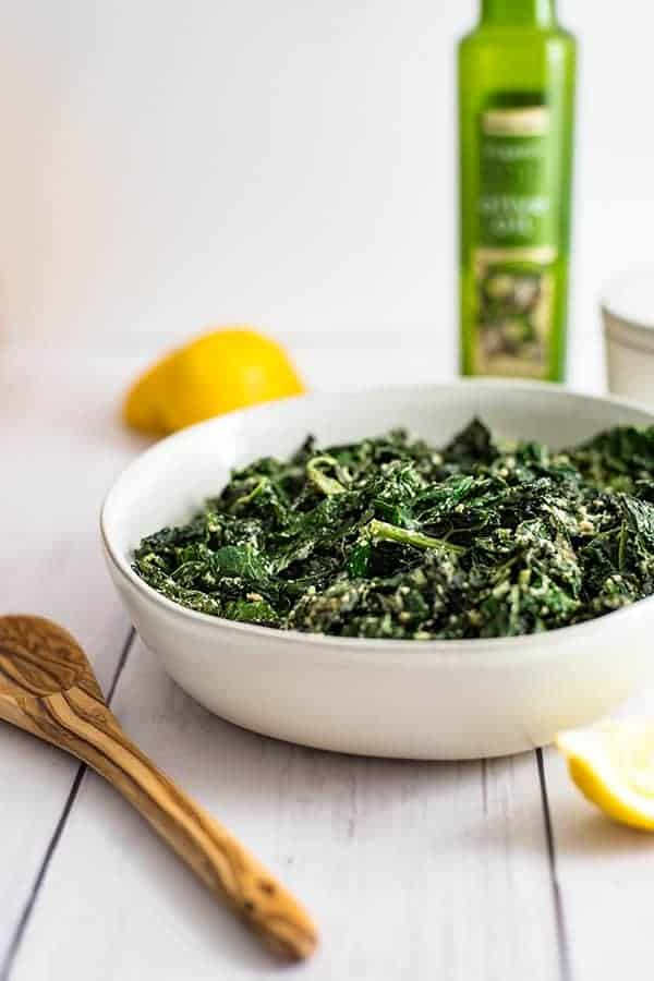 Bowl of creamy kale with a wooden spoon to the side