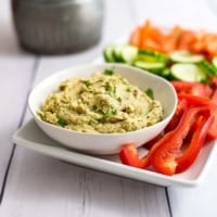 Bowl of roasted cauliflower hummus next to sliced red bell pepper on a white tray