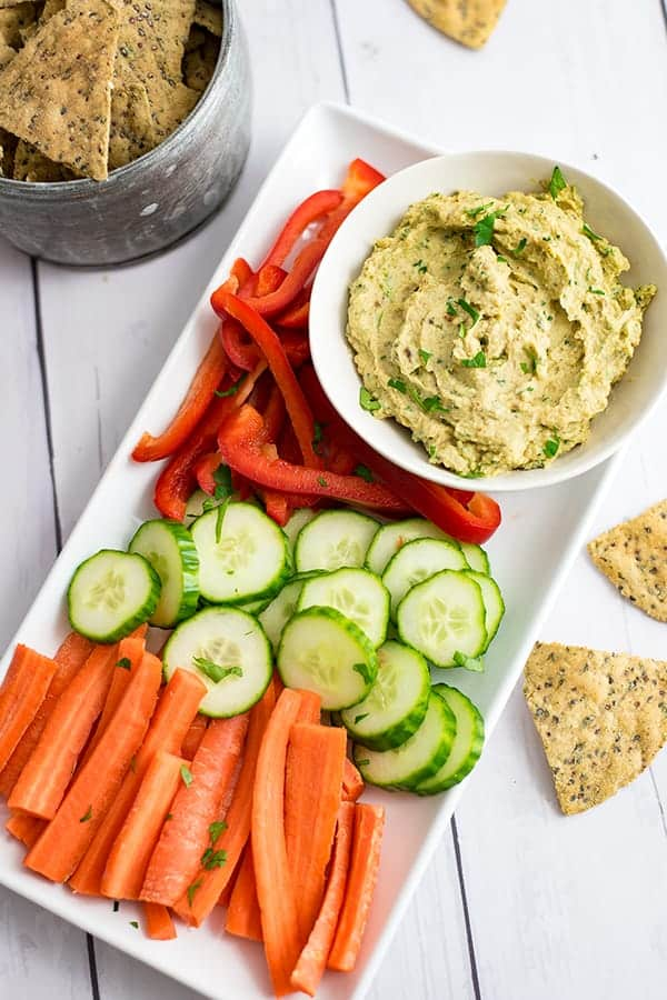 White platter with chopped carrots, cucumber and red bell pepper along a bowl of roasted cauliflower hummus