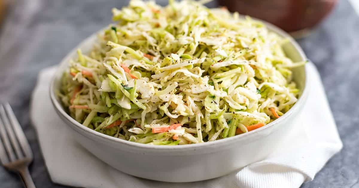 Large white bowl filled with paleo coleslaw over a white napkin.