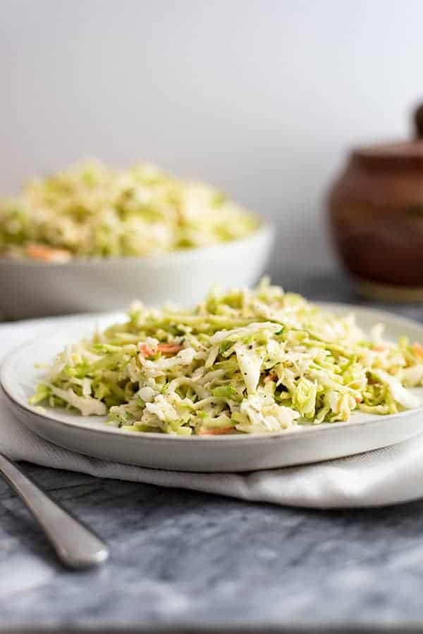 Paleo Coleslaw on a white plate over a white napkin. In the background there is a bowl of paleo coleslaw and a brown ceramic container