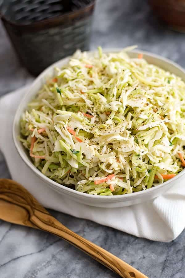 Large white bowl filled with paleo coleslaw over a white napkin and a wooden spoon.