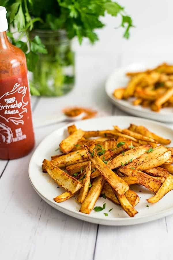 Cajun parsnip fries on a white plate with a bottle of sriracha next to them.