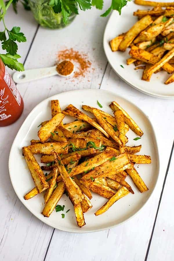 Cajun parsnip fries on a white plate with a teaspoon of cajun seasoning and an additional plate of parsnip fries in the background