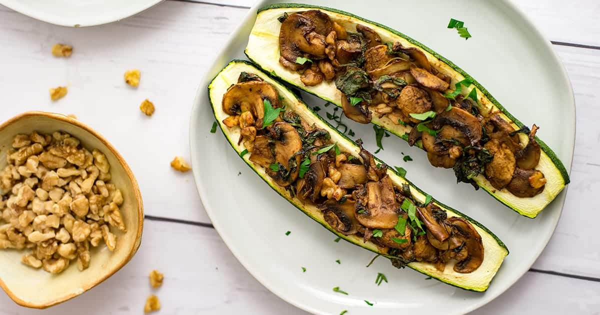 Small bowl of chopped walnuts next to two stuffed zucchini on an off white plate
