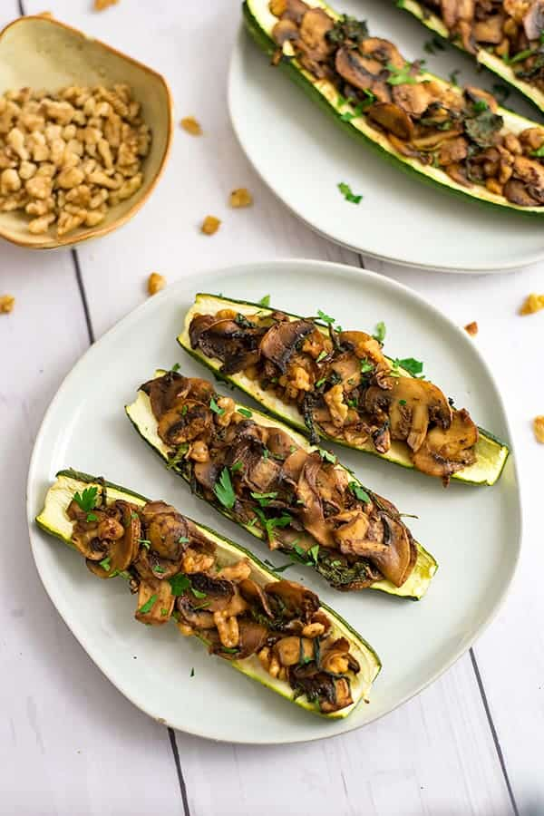 Three stuffed zucchini on an off white plate with a bowl of chopped walnuts in the background