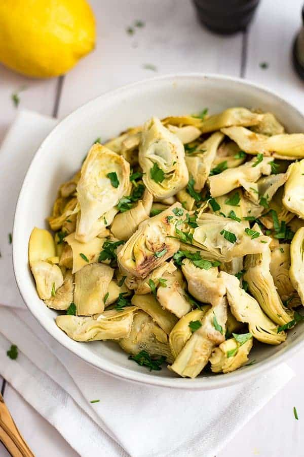 Large bowl filled with lemon artichokes with lemon in the background